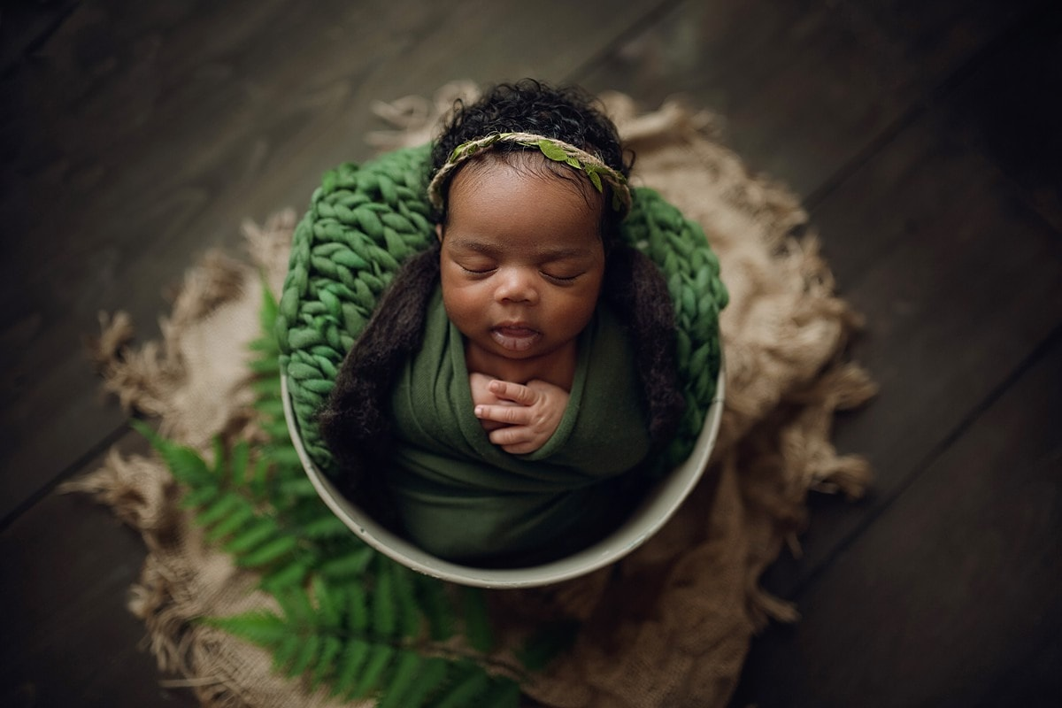 baby girl in green in bucket