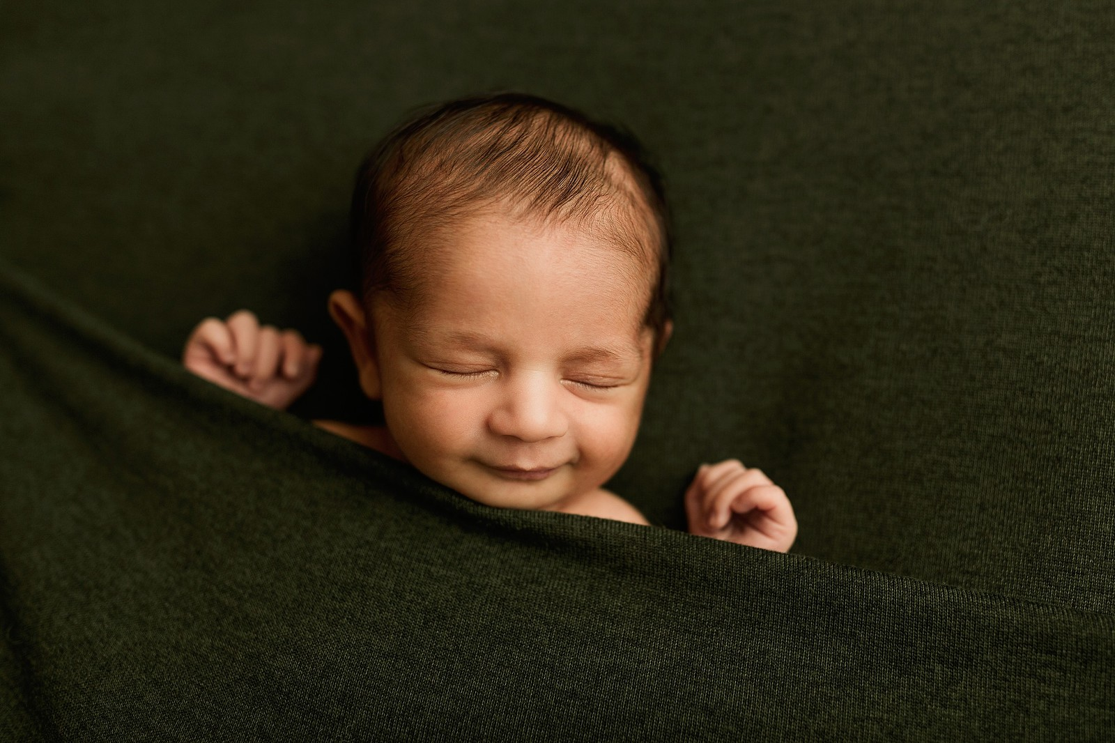 newborn smile nighty-night pose tucked in oshawa
