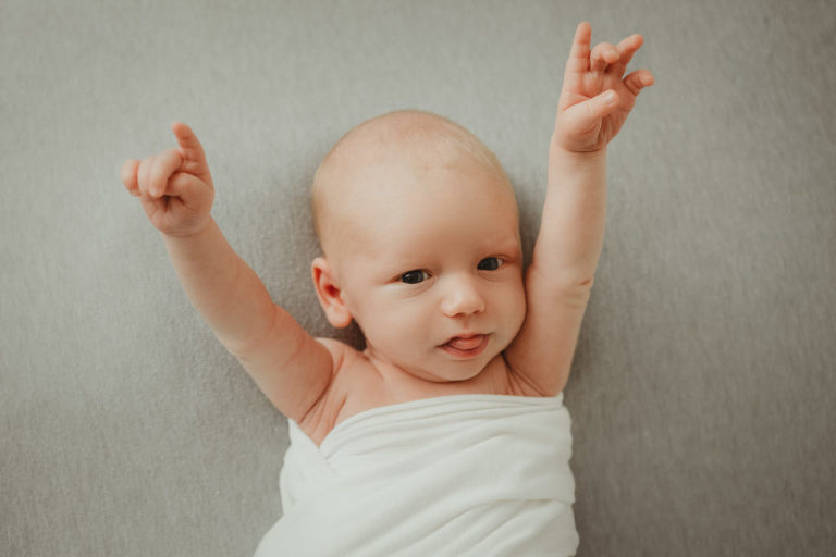 baby rocking out hands up